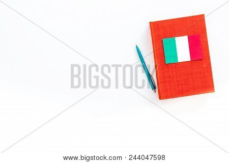 Language Study Concept. Textbooks Or Dictionaries Of Foreign Language Near Italian Flag On White Bac