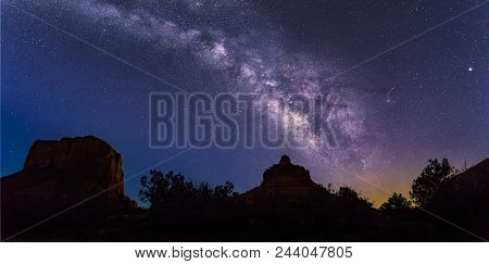 The Milky Way Galaxy Arcs Across The Sky From Bell Rock Over Courthouse Butte, To The Left, On A Dar