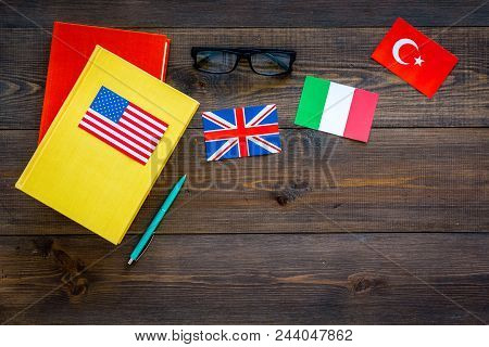 Language Study Concept. Textbooks Or Dictionaries Of Foreign Language Near Flags On Dark Wooden Back