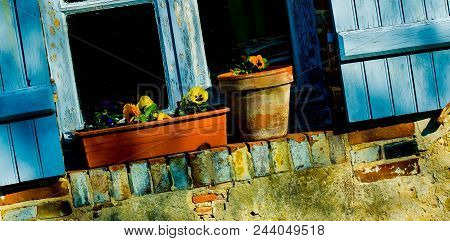 Potted Flowers Sitting On An Outdoor Windowsill With Blue Wooden Shutters In The French Countryside