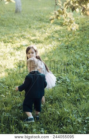 Children, Childhood, Family. Little Boy And Girl Play On Green Grass, Energy. Energy, Activity, Life