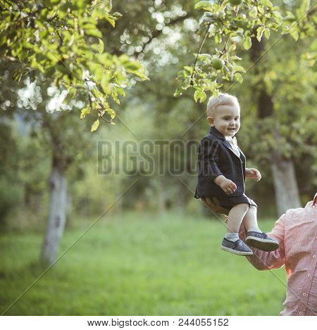 Trust, Love, Family. Small Boy Sit On Male Hand In Apple Garden, Trust. Cute Toddler Smile In Suit,