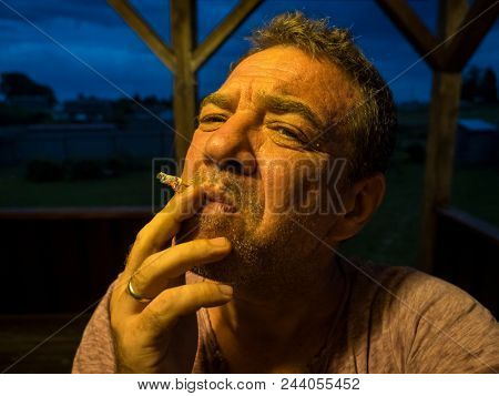 Middle-aged smoking man in the evening
