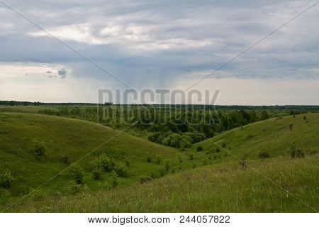 A Rain Cloud In The Field, In The Distance It Rains, Green Hills, A Beautiful Green Panorama Of The