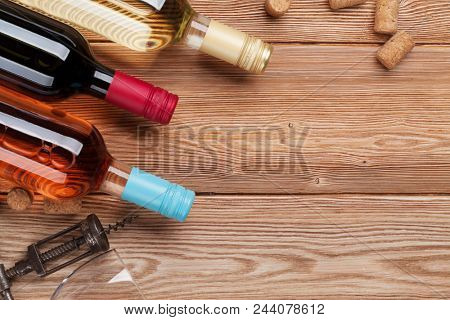 Wine bottles on wooden table. Red, rose and white wine. Top view with space for your text