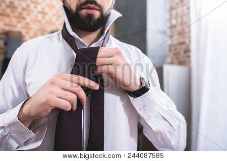 Cropped Image Of Loner Businessman Tying Necktie At Kitchen