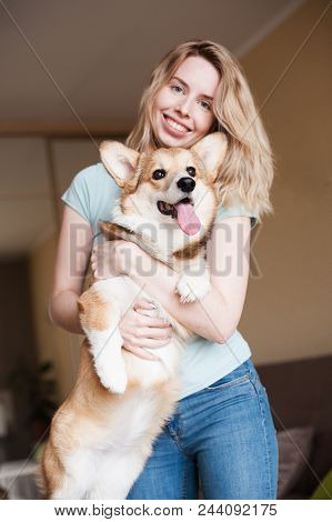 Young Woman Keeping Welsh Corgi Puppy Near Her Face. Welsh Corgi Pembroke Puppy, Happy Cute Dog.