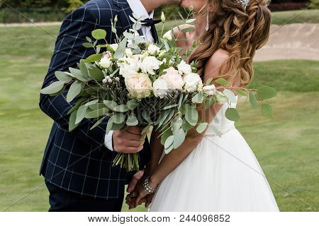 Happy Bride And Groom Holding Hands And Kiss On Wedding Ceremony Outdoors, Copy Space. Wedding Coupl