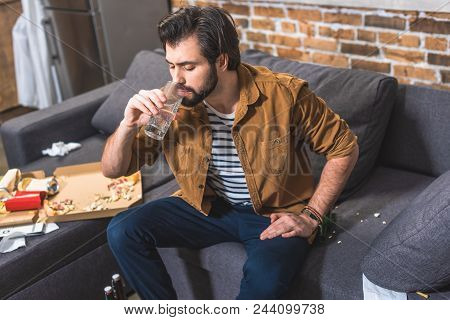 handsome loner drinking water and having hangover at living room poster