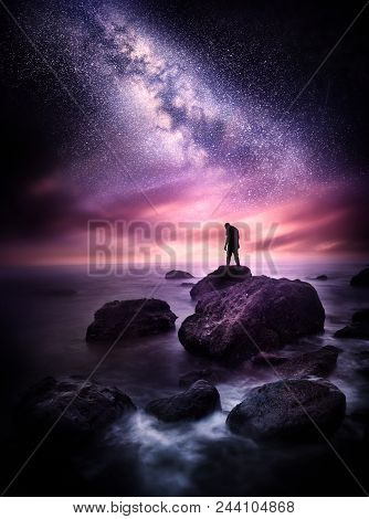 Night Time Sea Landscape With The Milky Way. A Man Stands On A Rocky Shore Line With The Stars Above