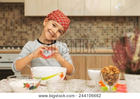 Cute Boy Shef Showing His Love While Cooking Holding A Heart Form For Biscuits In His Hansa And Smil