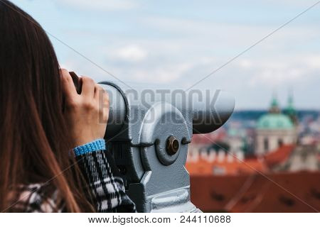 The Girl Looks Through The Binoculars On The Beautiful Architecture Of Prague On The Observation Sit