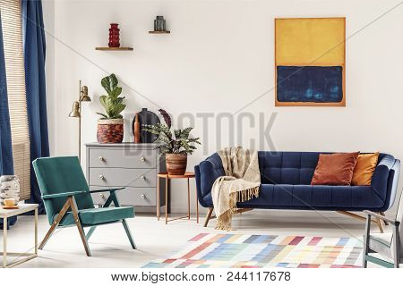 Orange End Table With Fresh Plant Standing Next To Navy Couch With Blanket And Pillows In White Livi