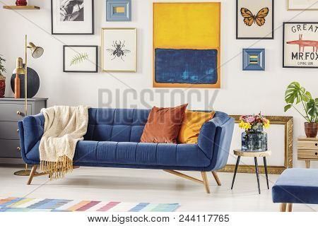 Real Photo Of A Navy Blue Couch With A Blanket And Orange Pillows Standing Against A White Wall With