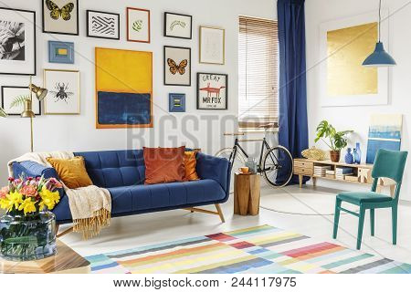 Spacious Living Room Interior With A Blanket And Orange Pillows On A Blue Sofa, Green Chair, Colorfu