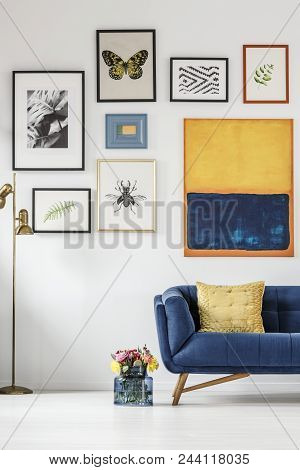 Fresh Flowers In Glass Vase Standing Next To Blue Sofa With Pillow In White Living Room Interior Wit