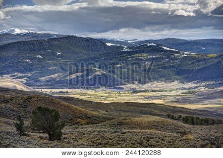 Wyoming Landscape With Hills, Sunlit Valley, And Mountains