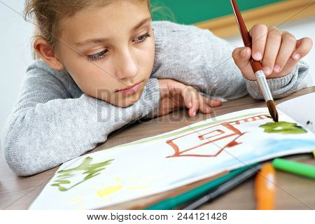 Disinterested Young Schoolgirl Is Drawing. Photo Of Unhappy Little Girl Doing Homework. Close Up. Ed