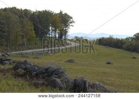 New Hampshire Dirt Road Curves Down  Hillside Of Muted Colors With Hazy Bluish Mountains In Distance