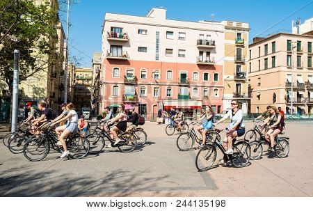 BARCELONA, SPAIN - APRIL 24, 2018: A group of tourists taking part of a bicycle tour by the popular La Barceloneta district in Barcelona, Spain