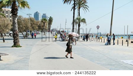 BARCELONA, SPAIN - APRIL 24, 2018: People walking and running by the seafront of the popular La Barceloneta beach in Barcelona, Spain, with the Mapfre Tower and the Hotel Arts in the background