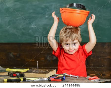 Toddler Holds Protective Hard Hat, Helmet By Wrong Side, Chalkboard Background. Child Cute And Adora