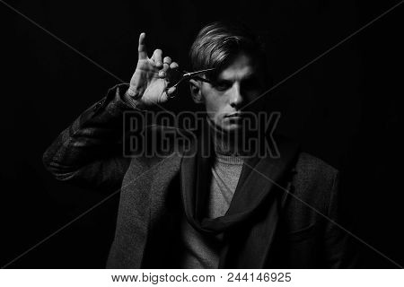 Stylist in suit and scarf on black background. Man in vintage style with scissors in his hand. Guy with scissors near eye. Hairdresser with serious face. Business and barbershop concept. poster