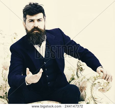 Man With Beard And Mustache Wearing Classic Suit, Sits On Old Fashioned Armchair Or Sofa. Macho Attr