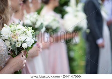Wedding Bouquets In The Hands Of The Witnesses At The Wedding Ceremony