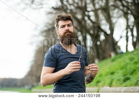 Guy Looks Cool With Stylish Sunglasses. Eye Protection Concept. Man With Beard And Mustache Holds Su