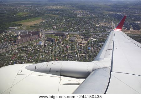 Wing Of The Aircraft Over The City And Houses. The Plane Is Landing.