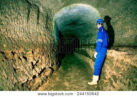 Underground Work. Hunched Worker In A Blue Overall And A Safety Helmet Stands In The Underground Tun