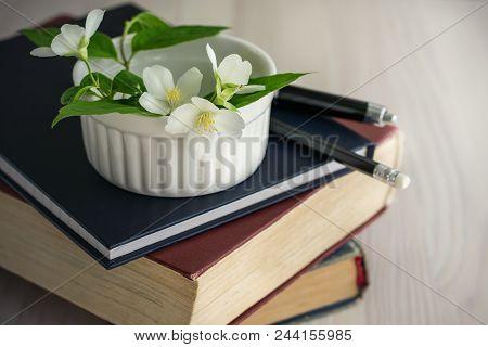 Reading A Sentimental Novel. A White Jasmine Flower On A Pile Of Books.
