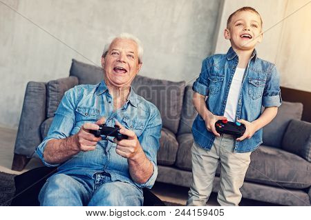 Emotional Players. Cheerful Happy Emotional Moment Of Two Relatives Playing Wonderful Games At Home