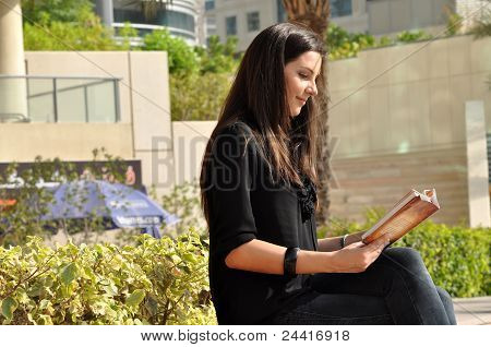 Young Beautiful Woman Reading A Book