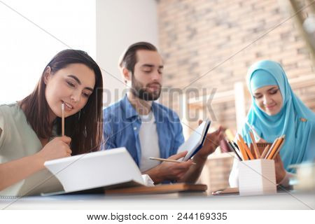 Muslim student with classmates in library