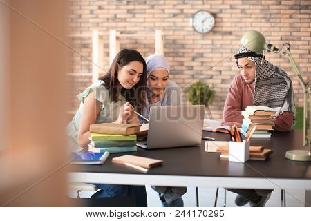 Muslim students with their classmate in library