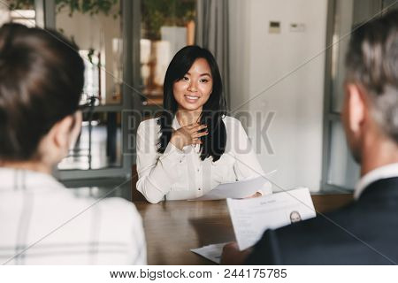 Business, career and placement concept - young asian woman smiling and holding resume while sitting in front of mentor or managers during job interview