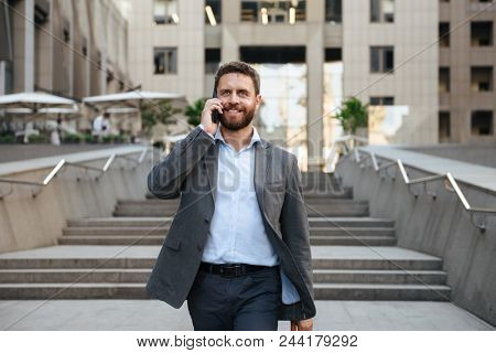 Portrait closeup of happy business man 40s in gray suit speaking on mobile phone while walking down stairs outside modern business center