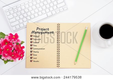 Project Management And Check List Marks In Notebook With Keyboard, Pencil And Coffee Cup On White Ta