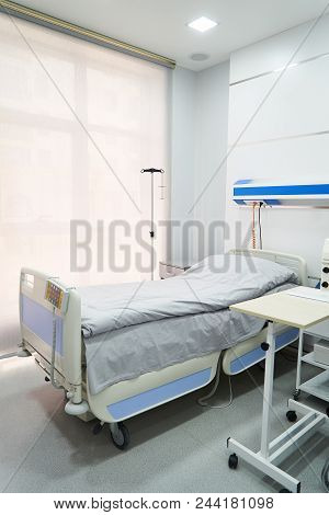Empty Bed On Hospital Ward. Hospital Room With Bed And Comfortable Medical Equipped In A Modern Hosp