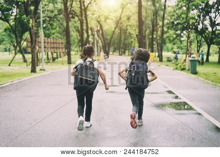 Two Pupils Of Primary School Run Go To Shool. Two Girl With Bags Behind The Back. Warm Day Of Fall.