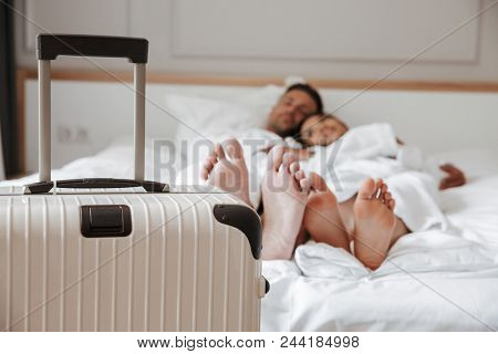 Blurry image of beautiful couple man and woman in white bathrobe lying and resting together on bed in hotel room with big baggage in foreground. Holiday concept poster