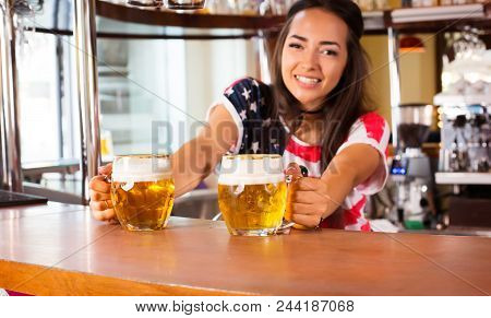 Young Cheerful Happy Bartender Girl Looking At Camera And Offering Beer To Customers. Happy Smiling