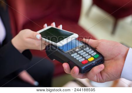 Female Paying With Nfc Technology On Smart Phone, Hands Close Up. Woman Using Mobile Phone For Pay B