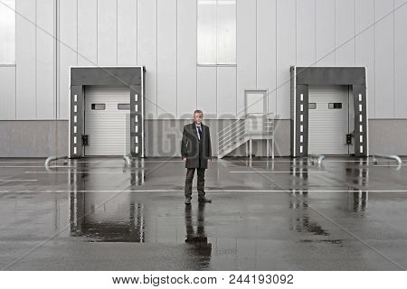 Businessman In Front Of Distribution Warehouse Loading Dock