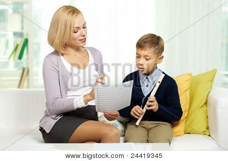 Portrait of pretty tutor showing notes diligent pupil with the flute
