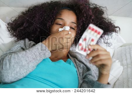 Sick African American Girl With Flu Virus In Bed At Home. Ill Young Black Woman With Cold Reading Dr
