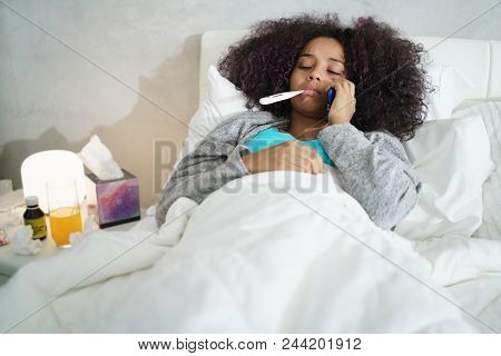 Sick African American Girl With Flu In Bedroom At Home. Ill Young Black Woman With Cold Calling Doct