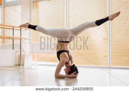 Lovely Young Woman In Sportswear Performing Difficult Yoga Pose On Floor In Light Studio
